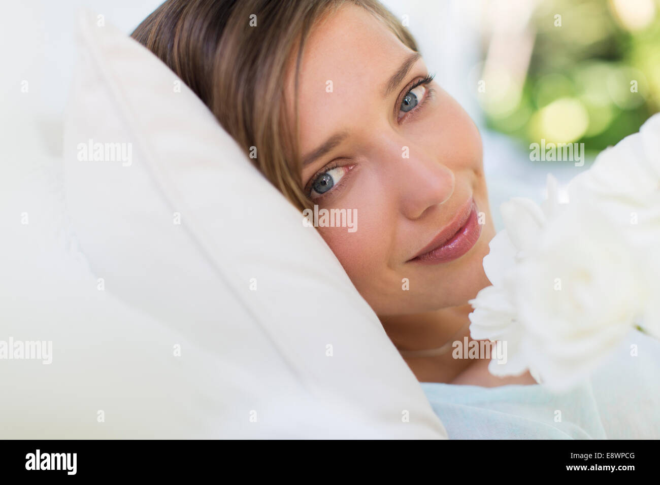 Close up of woman smelling flower on bed Stock Photo