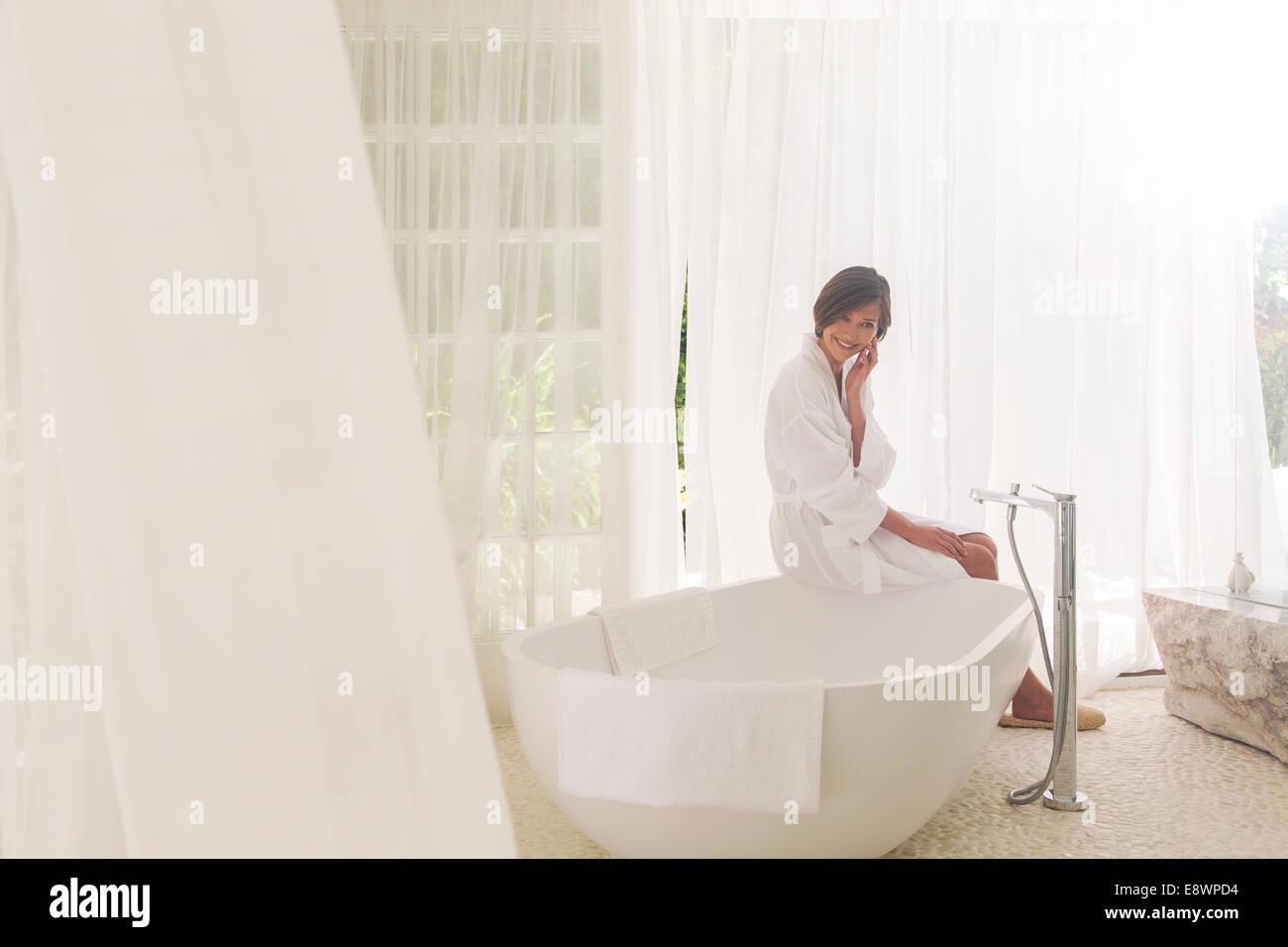 Woman Running Bath In Modern Bathroom