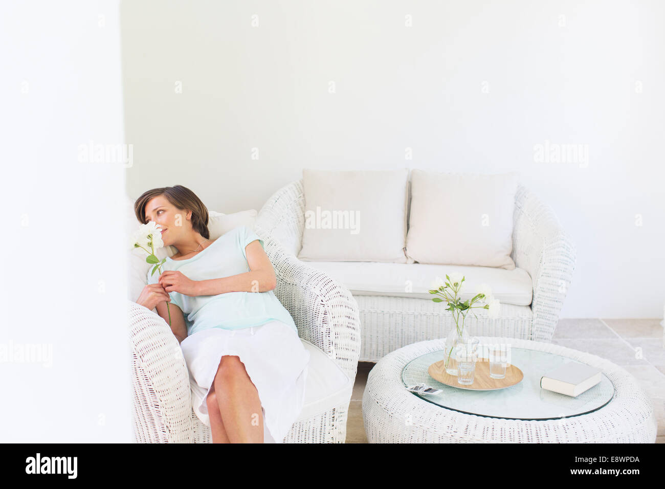 Woman smelling flowers in wicker chair in living room Stock Photo ...
