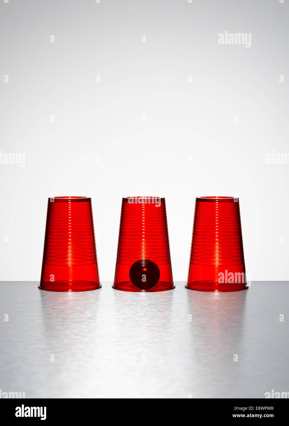 Ball under middle of three clear red cups Stock Photo