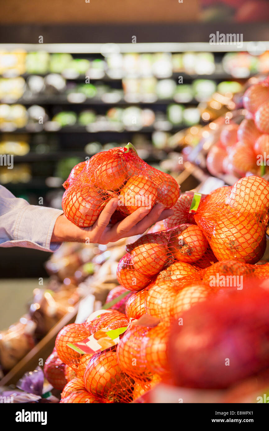 Close up of man holding bag of onions in grocery store - Stock Image