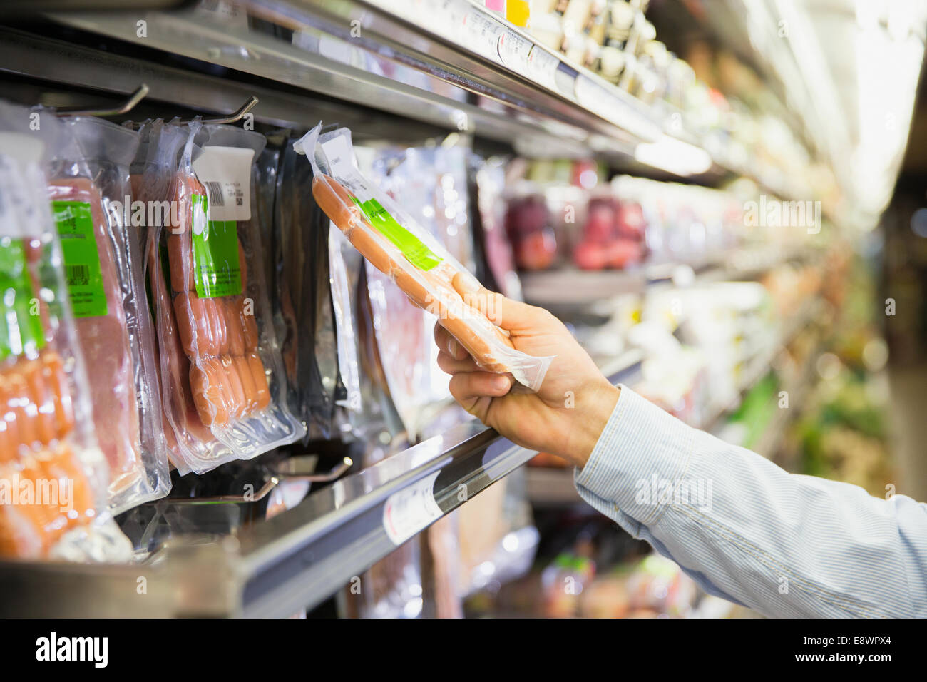 Man selecting product in grocery store - Stock Image