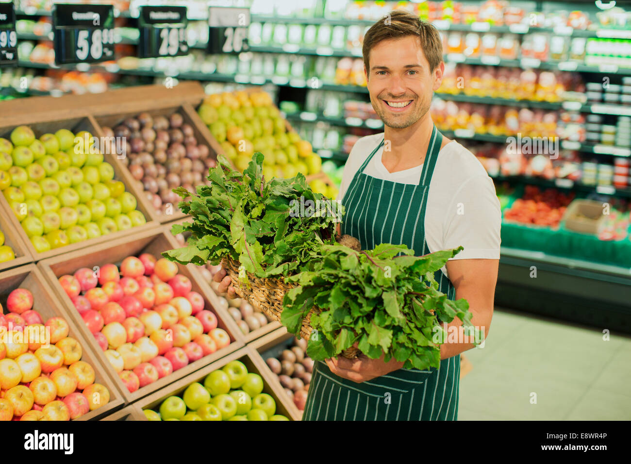 clerk carrying produce in grocery store stock photo