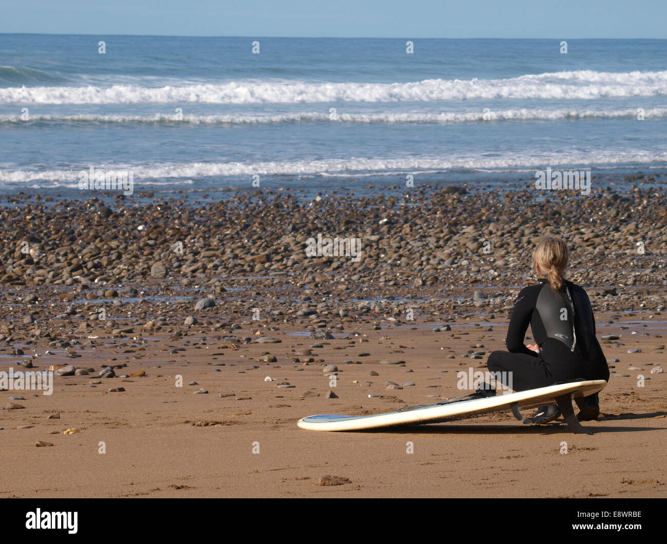 Surfer crouched on the beach watching the waves, Widemouth Bay, Bude, Cornwall, UK Stock Photo