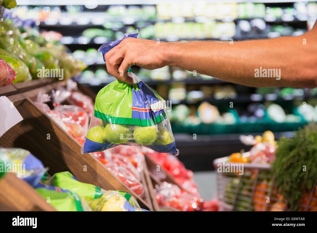 Man holding bag of produce in grocery store - Stock Image