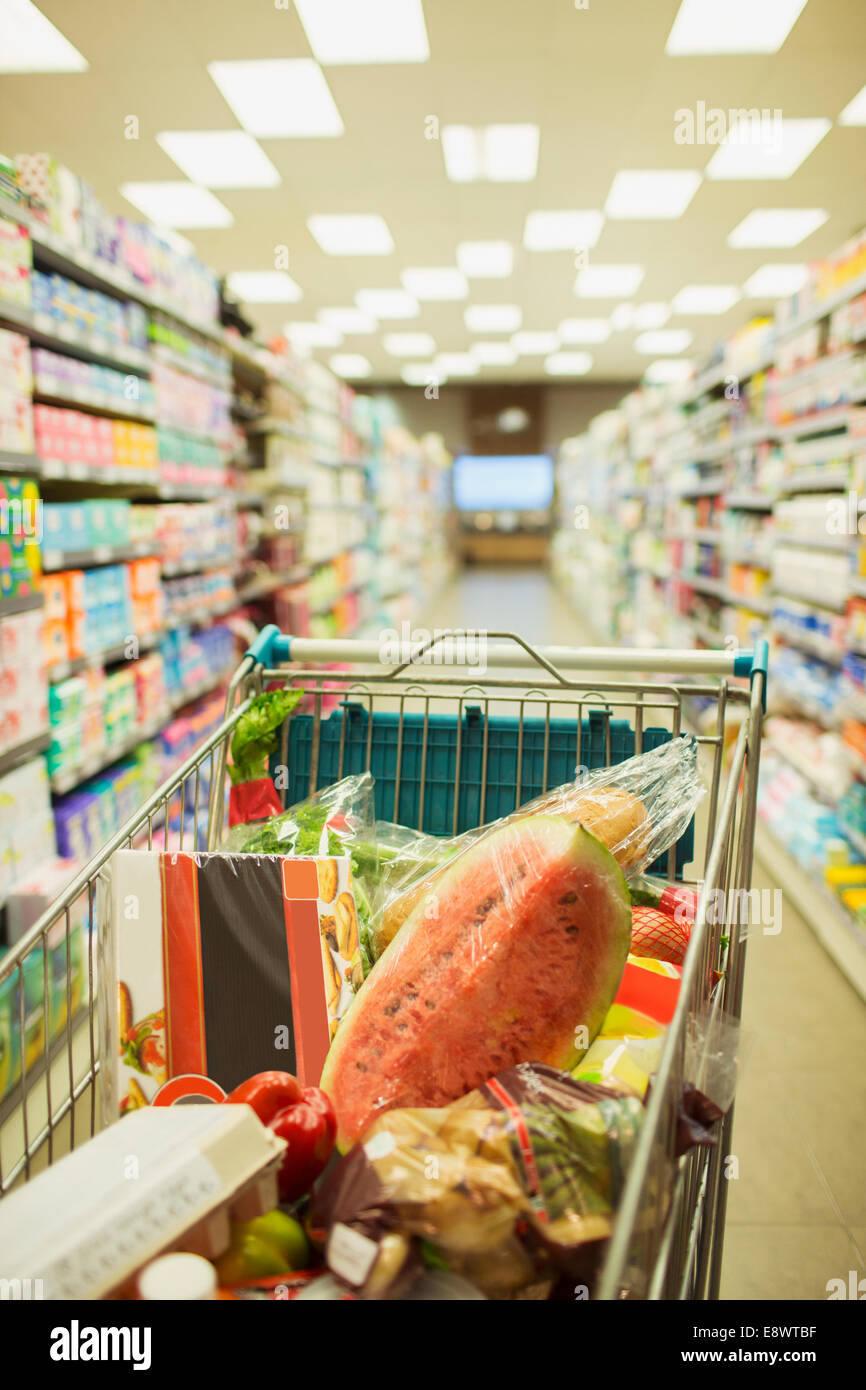 Full shopping cart in grocery store aisle - Stock Image