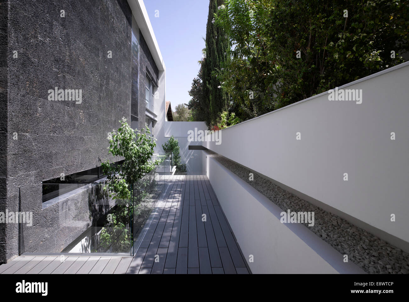 Wooden walkway with white recessed wall and exterior of H House, Israel, Middle East. - Stock Image
