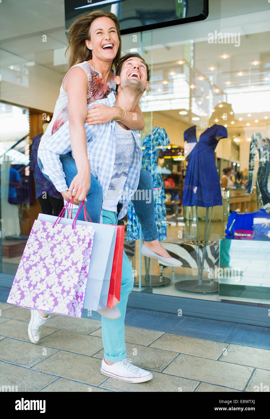 Man carrying girlfriend piggyback outside clothing store Stock Photo