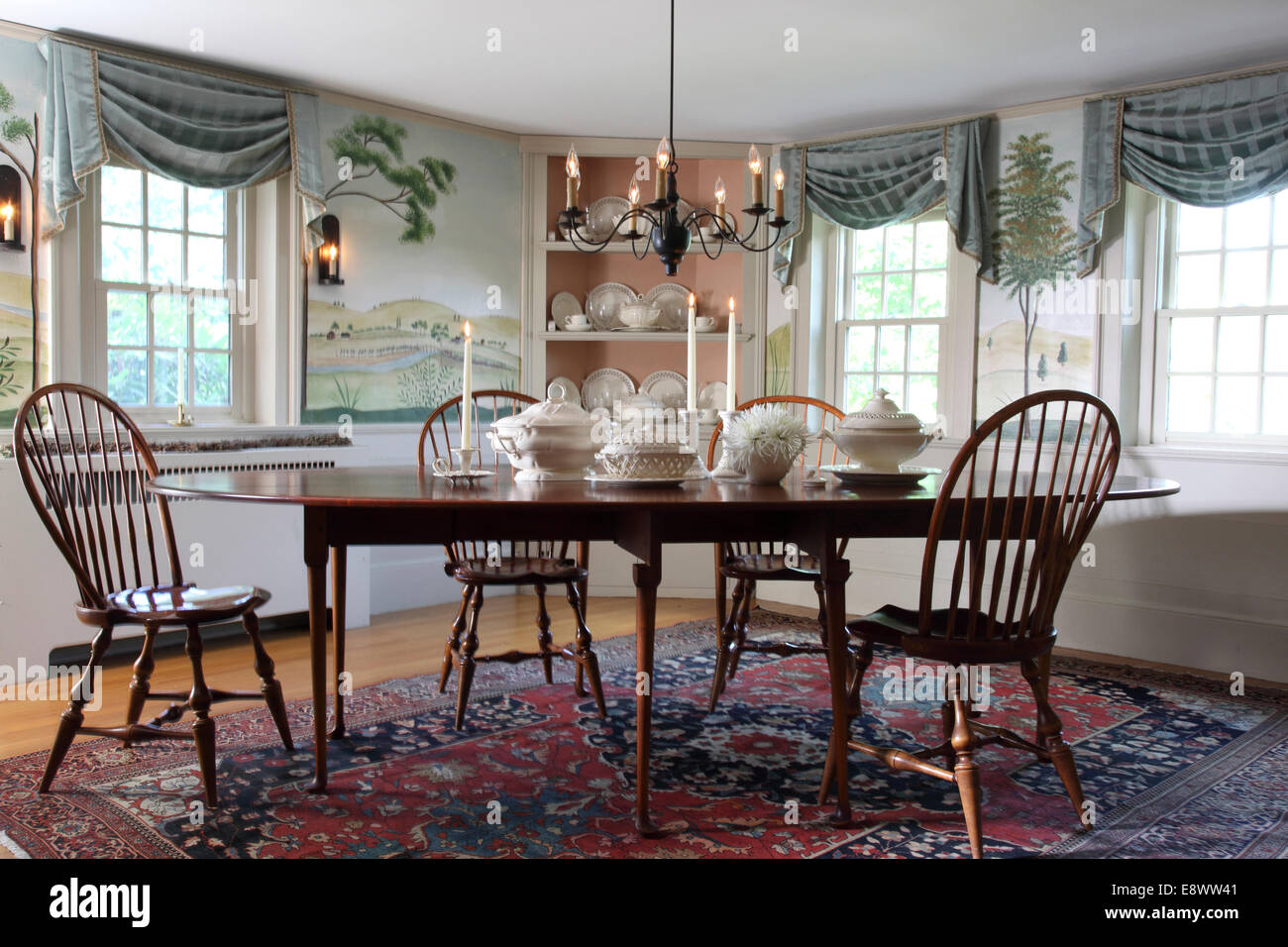 Dining Room With Wall Mural Of Countryside In Folk Art Style Table White China Serving Bowls And A Built Corner Cabinet Displaying
