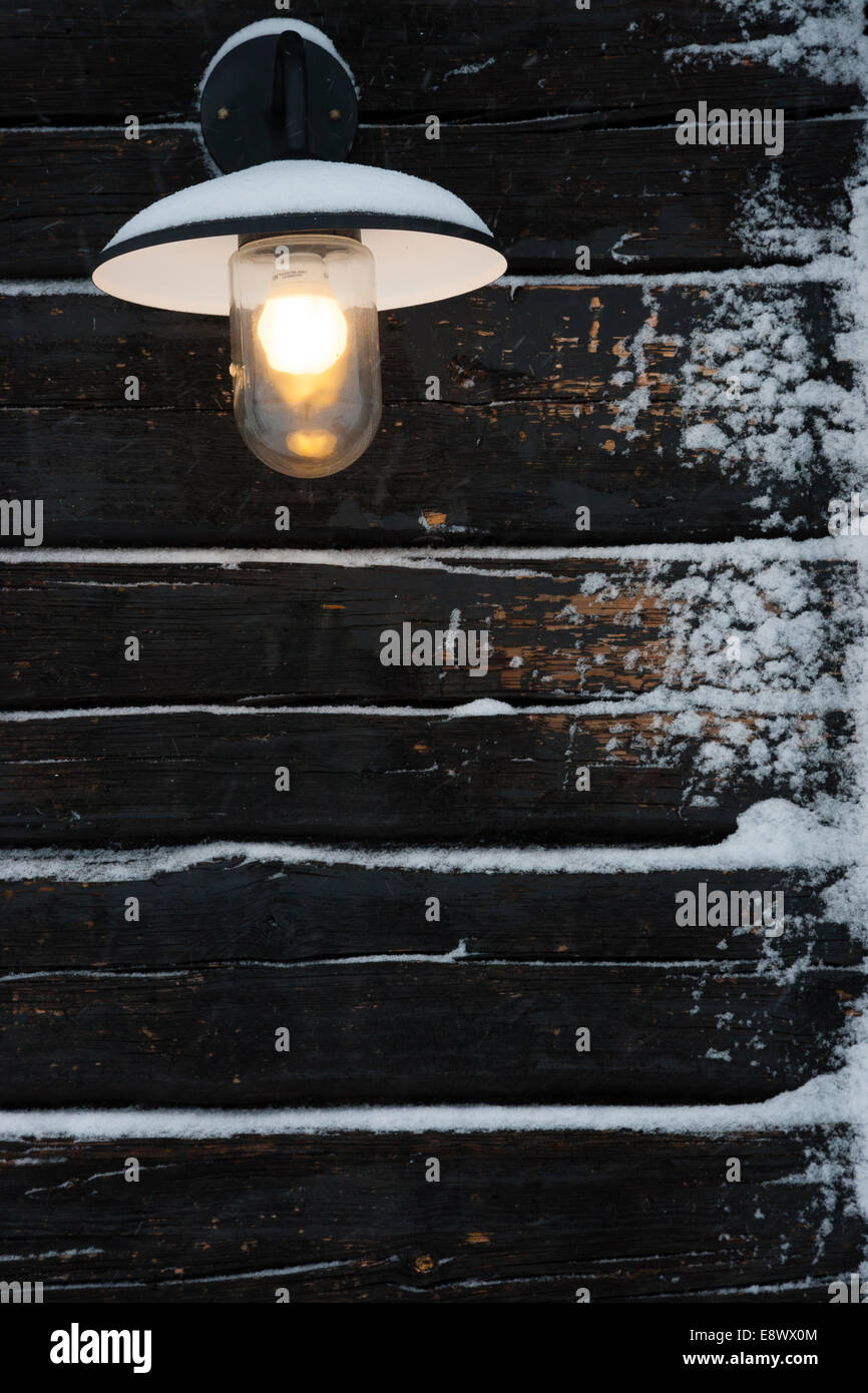 JAVRE, SWEDEN Detail of electric light hanging on wooden cabin in snow. Stock Photo