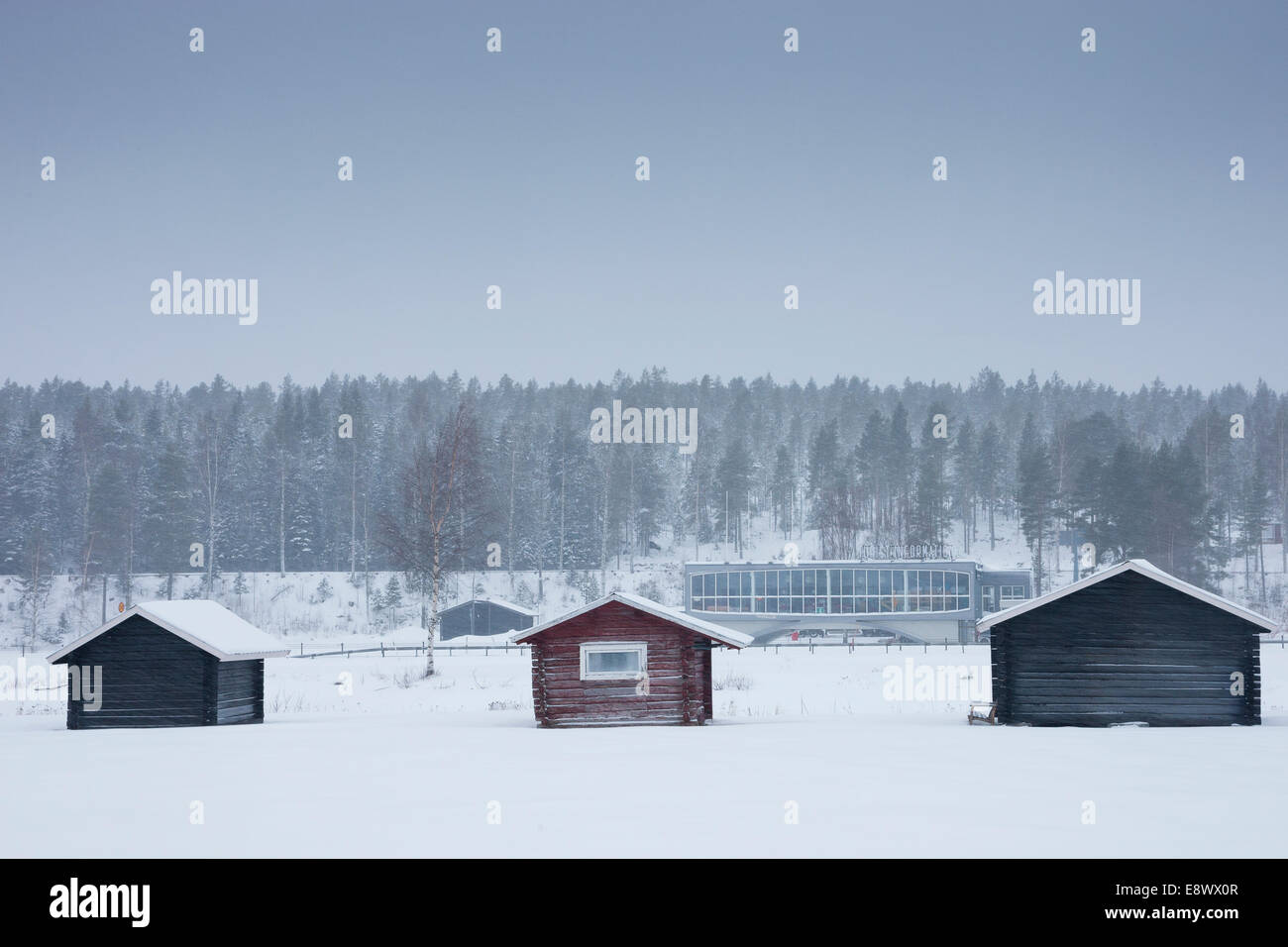 JAVRE, SWEDEN Motorway service station behind traditional wooden structures in snow. Stock Photo