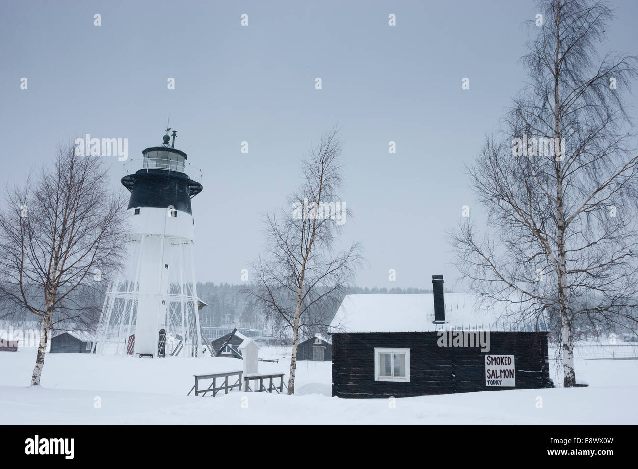 """JAVRE, SWEDEN """"Smoked salmon today"""" sign on wooden cabin with lighthouse in background. Stock Photo"""