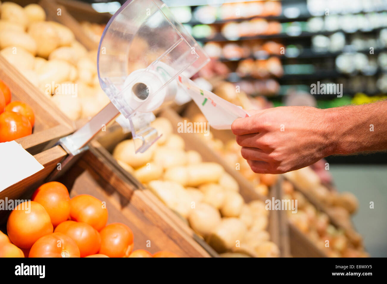 Close up of man taking plastic bag in produce section of grocery store - Stock Image