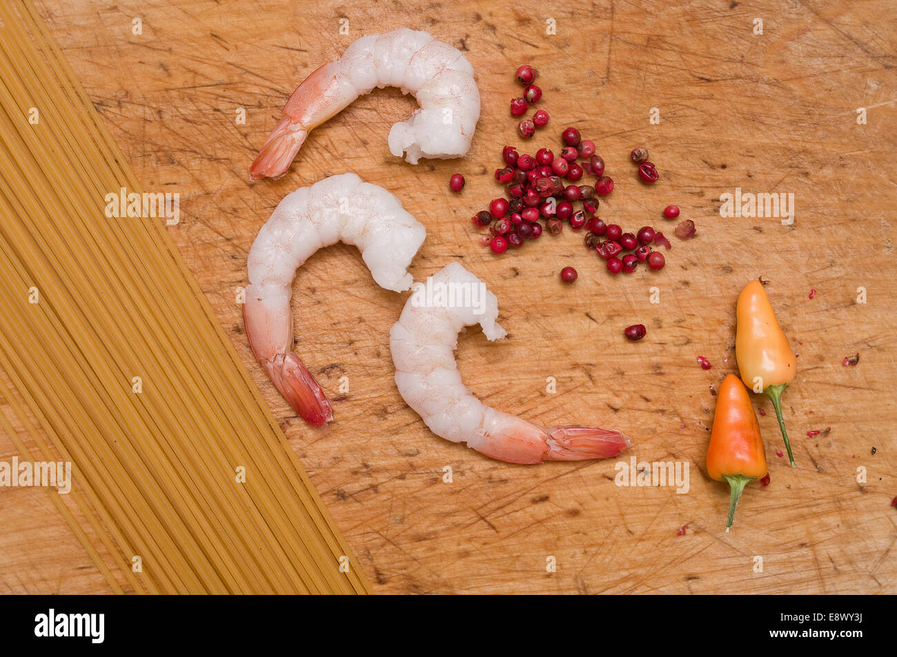 Ingredients for recipe of pasta with spicy shrimp and tomato sauce, on a wooden chopping board - Stock Image