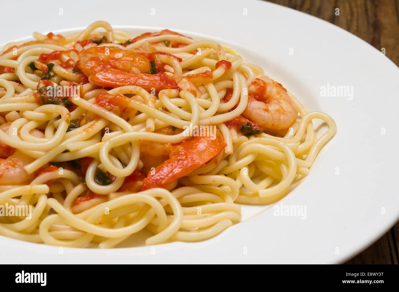 Pasta with spicy shrimp and tomato sauce on a wooden table - Stock Image