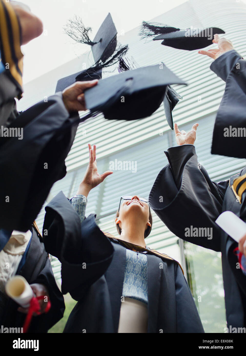 Students in gowns throwing caps in the air - Stock Image