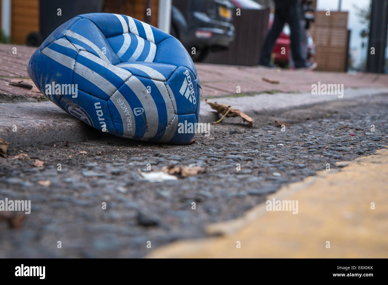 deflated football in the gutter - Stock Image