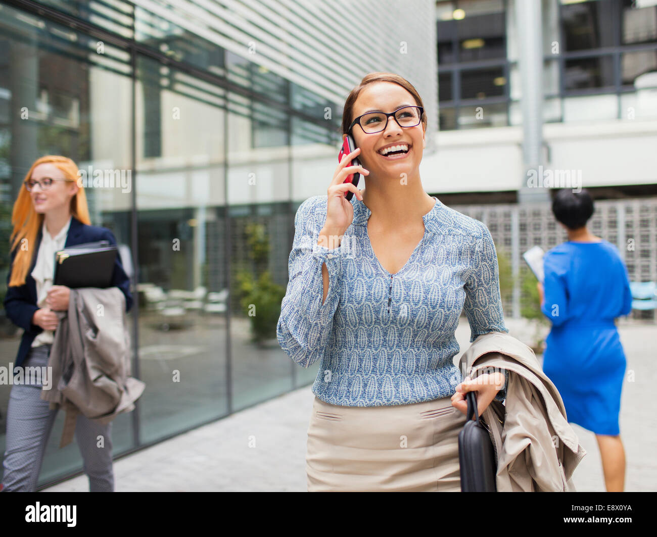 Businesswoman talking on cell phone outside of office building - Stock Image
