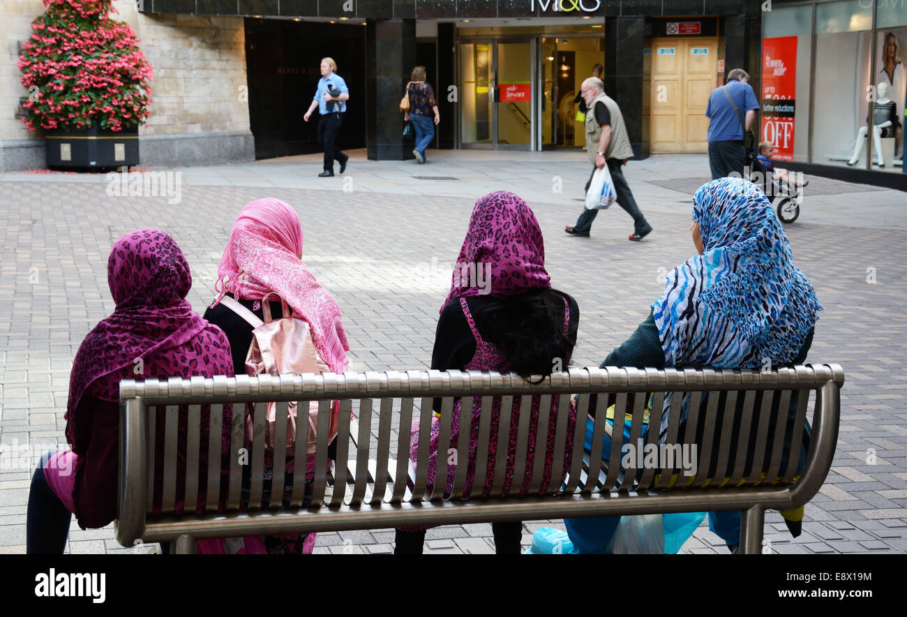 Four Muslim women on a seat, all with hijab, Nottingham, England. - Stock Image