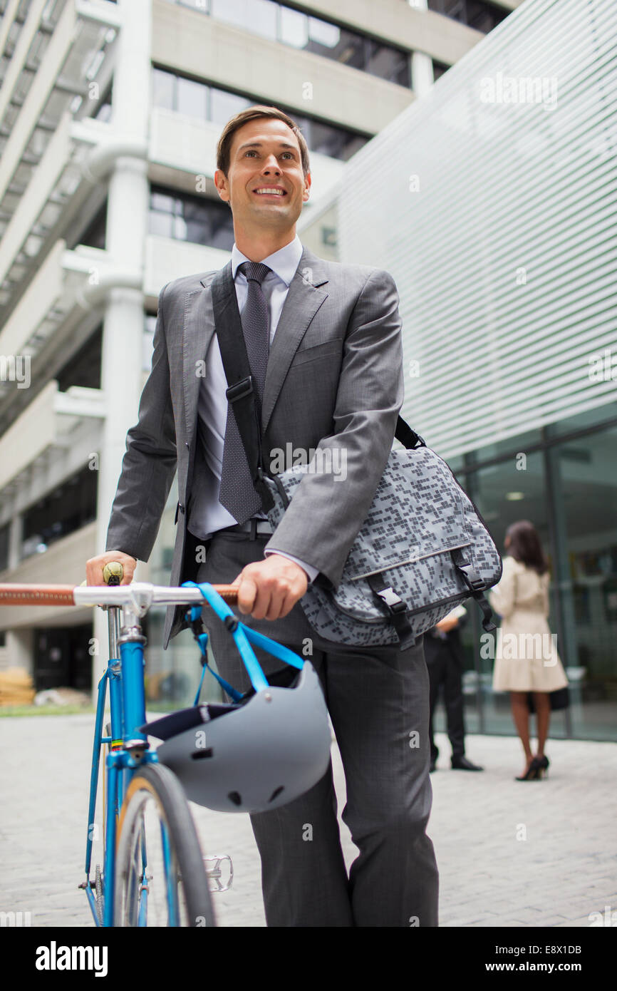 Businessman walking bicycle outside of office building - Stock Image