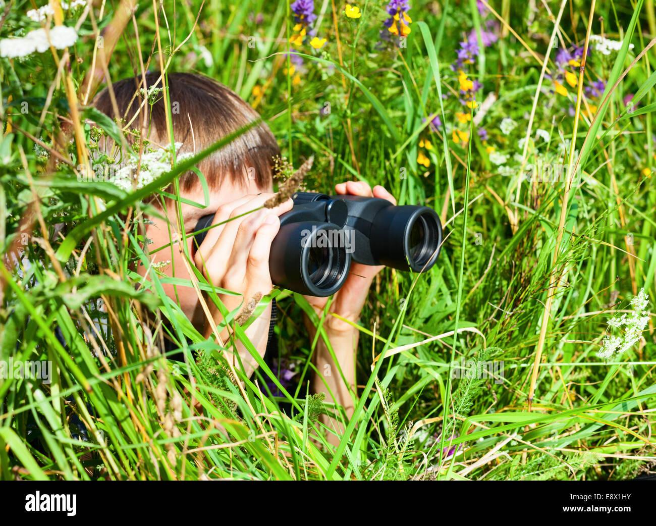 Boy hiding in grass looking through binoculars outdoor - Stock Image