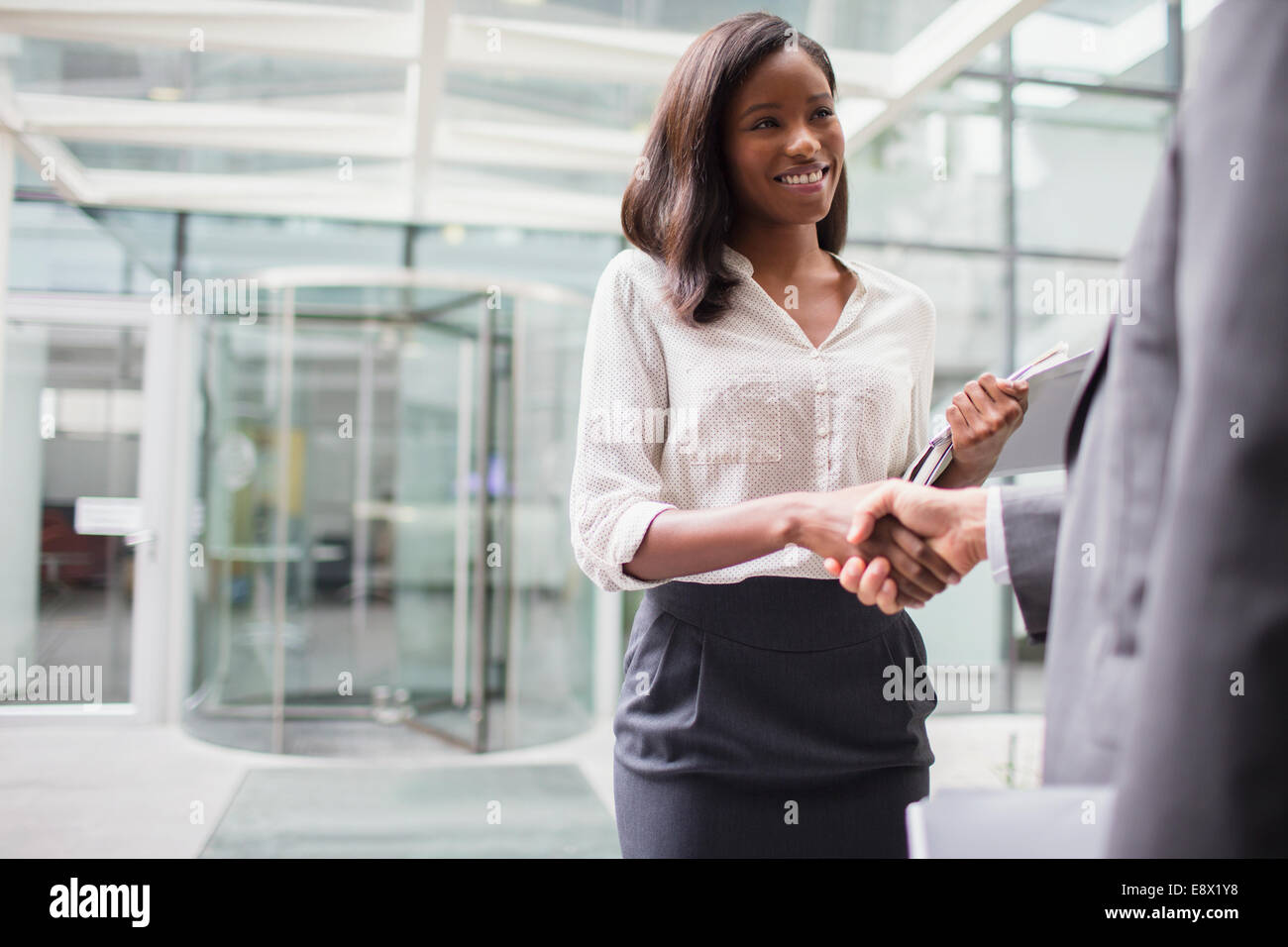 Business people shaking hands outside of office building - Stock Image