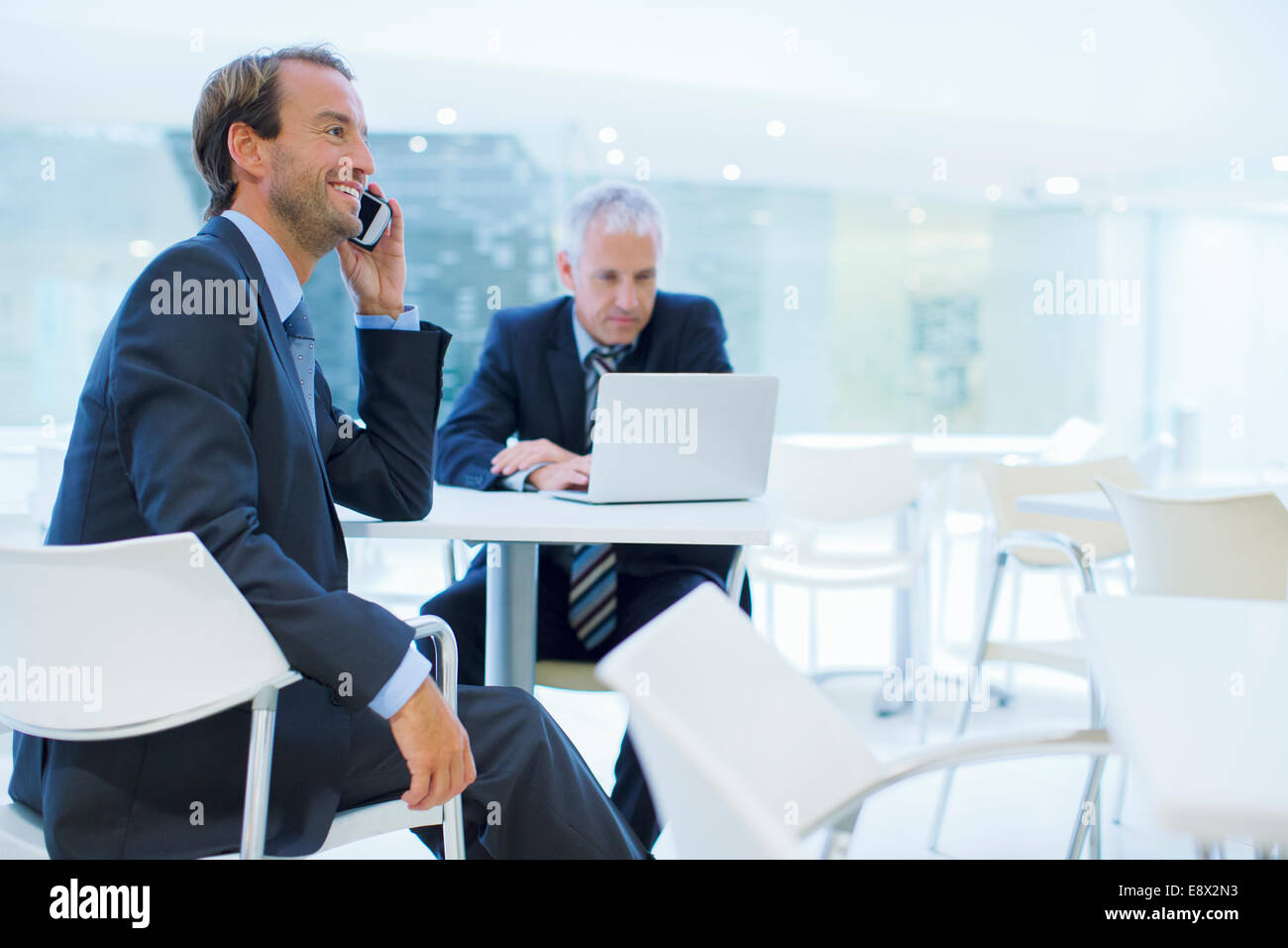 Businessman talking on call phone in office building cafe - Stock Image