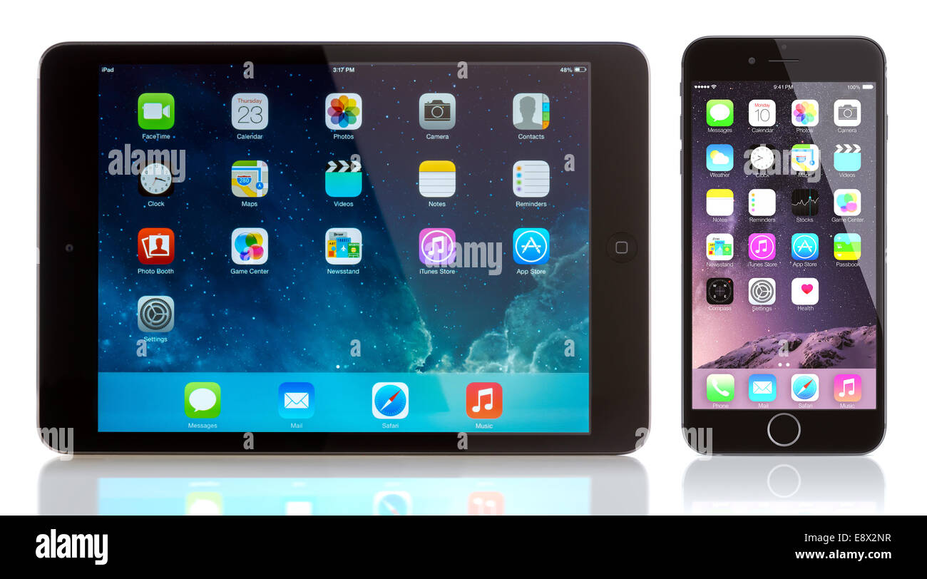 iPad Mini and iPhone 6 on white. Apple iOS 8 applications on the home screen of the iPhone 6 Stock Photo