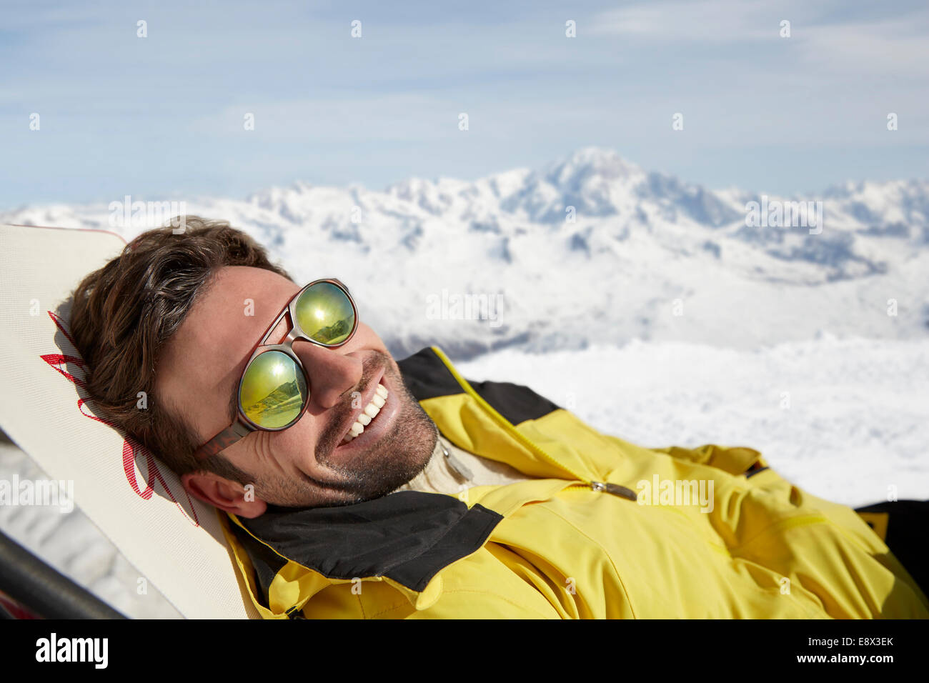 Man laying on a chair in the snow - Stock Image