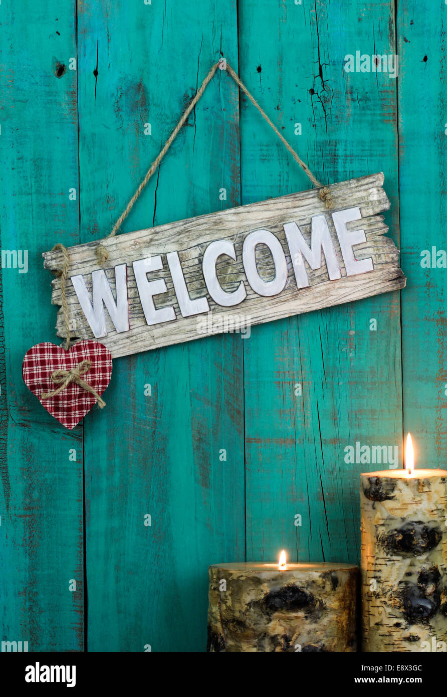 Wooden welcome sign with red plaid heart and burning candles hanging on antique teal blue weathered background - Stock Image