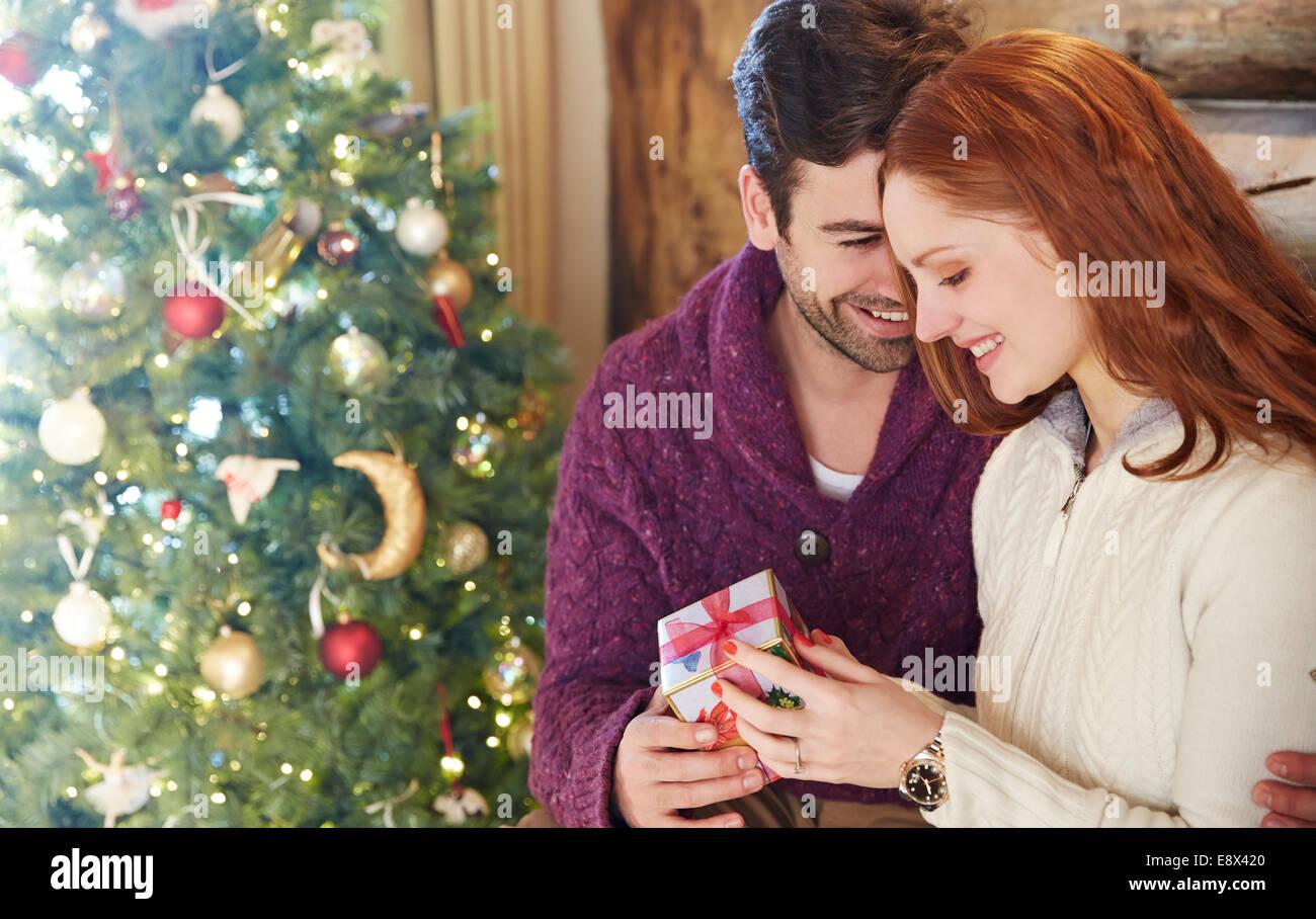 Couple exchanging gifts on Christmas - Stock Image