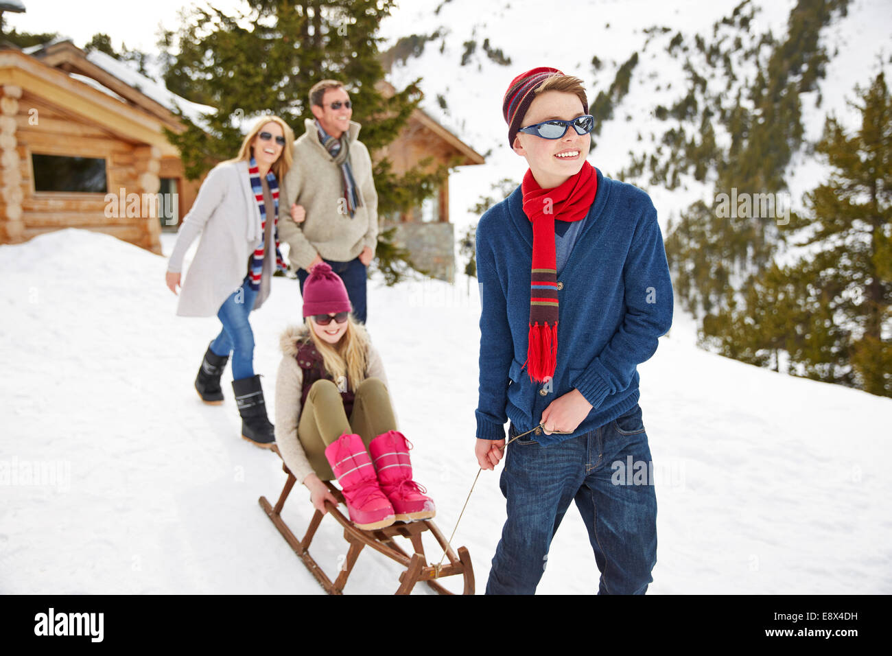 Brother pulling sister on sledge in snow - Stock Image