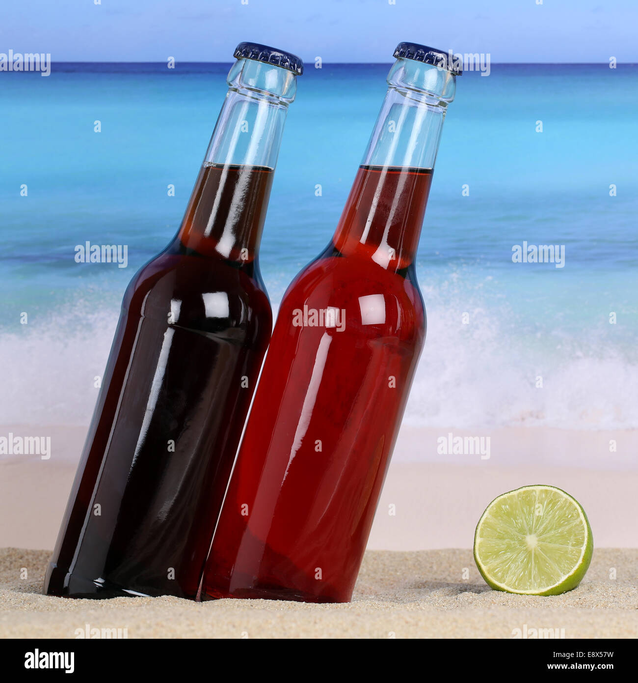Cola and lemonade soft drinks on the beach in sand and sea - Stock Image