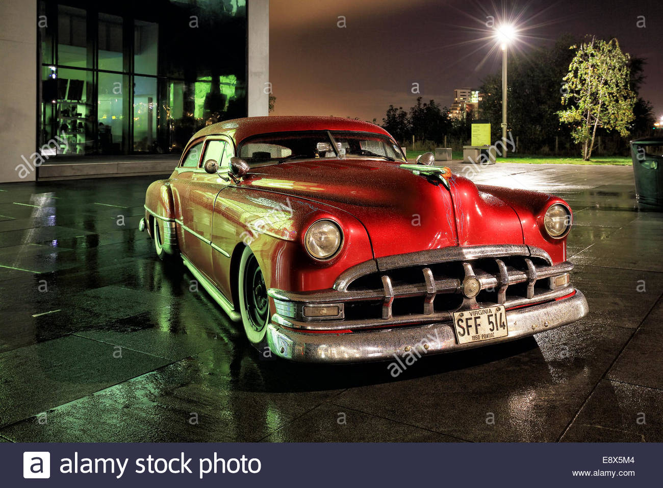 Night shot of a classic Pontiac 1950 outside the Glasgow Riverside Transport Museum reflecting on the rain soaked - Stock Image