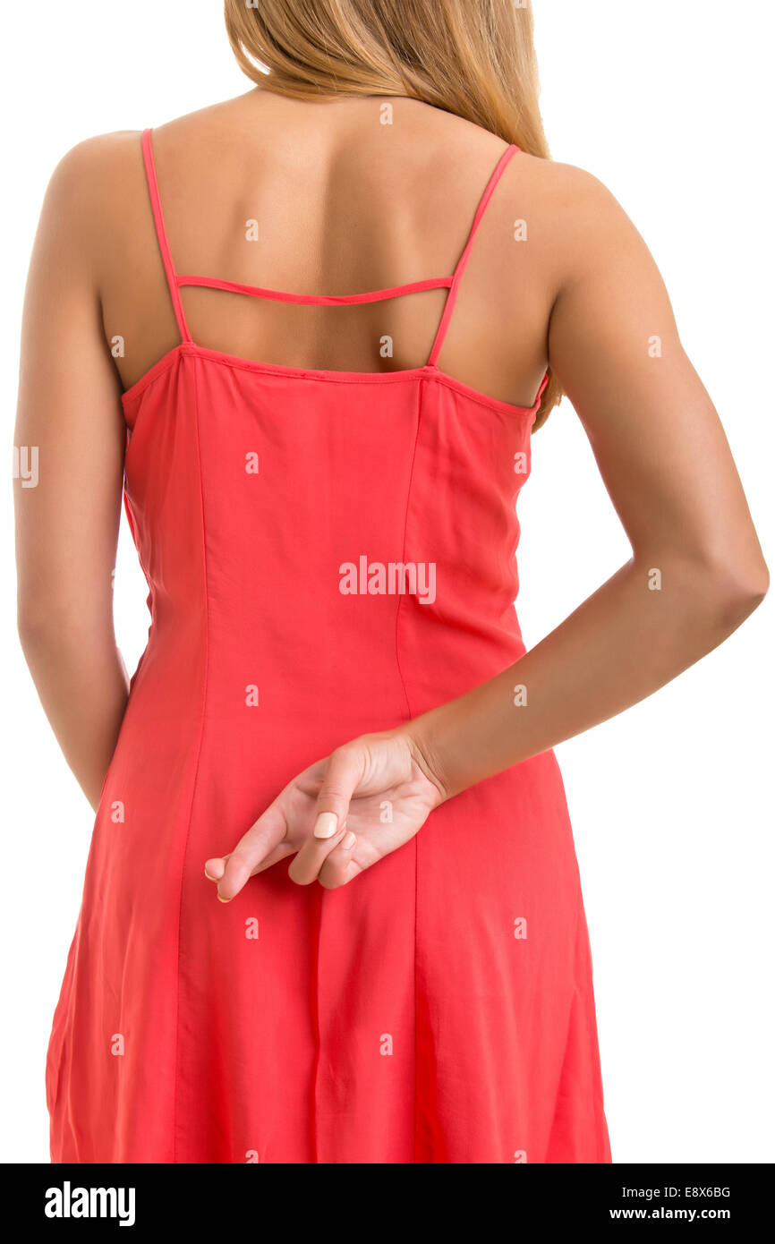 Close up of crossed fingers behind a woman's back - Stock Image