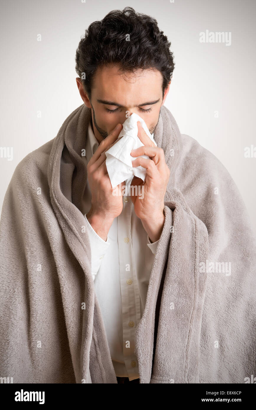 Pale sick man with a flu, sneezing, in a clean background - Stock Image