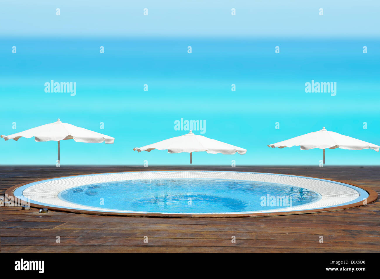 Empty jacuzzi facing a beach with a blue ocean - Stock Image