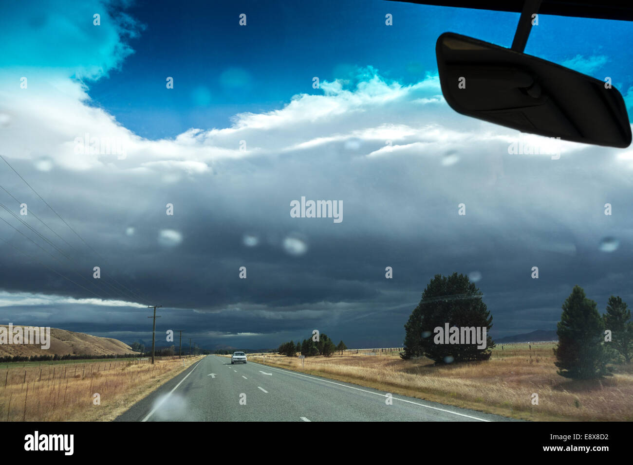 New Zealand weather can be unpredictable. Driving into a rainstorm on Highway 8 near Omarama. First rain drops on - Stock Image