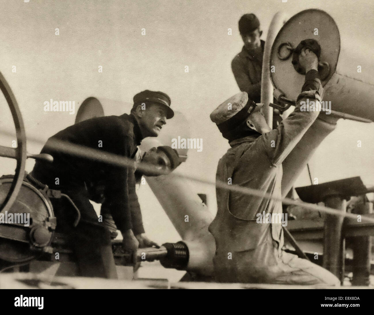 The fuse is set as Chief Petty Officer leads a crew of four in loading a Y-Gun with Mark-3 anti-submarine depth - Stock Image