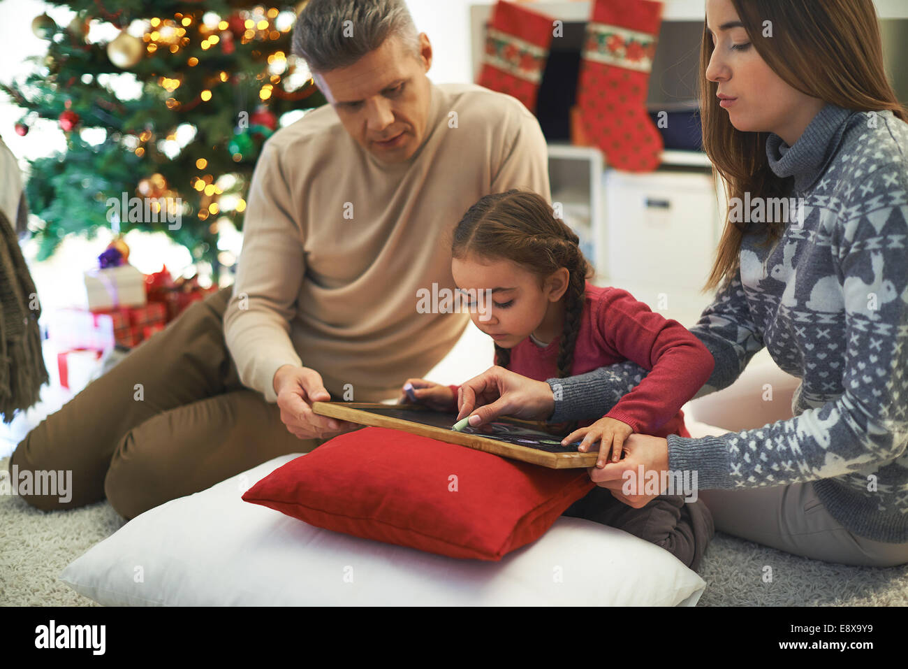Man and woman teaching their daughter how to write - Stock Image
