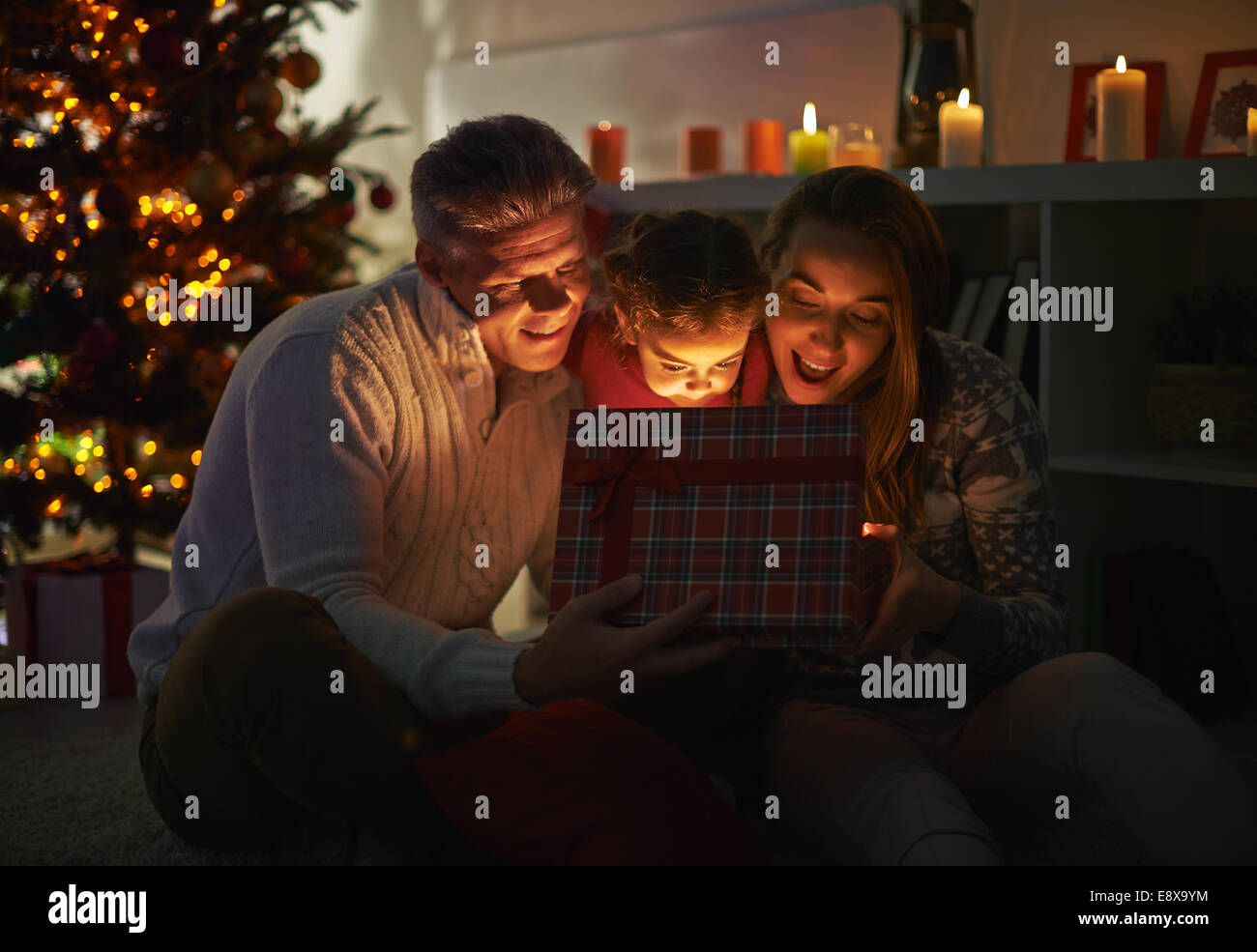 Happy family of three looking into open giftbox on Christmas night - Stock Image