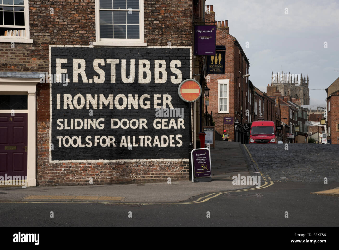 Large clear hand-painted ghost sign, an old advertisement for an ironmonger's, on the side of a brick building - Stock Image