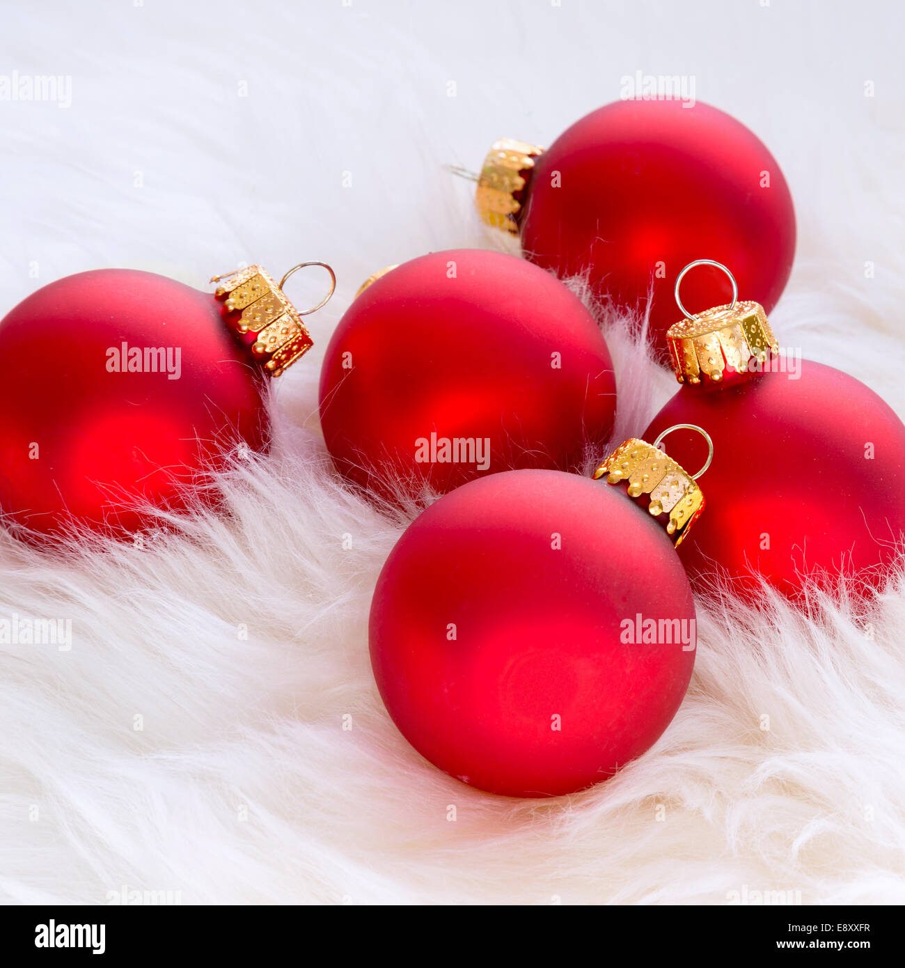 Red Glass Christmas Ornaments In A Background Of Soft White Fur