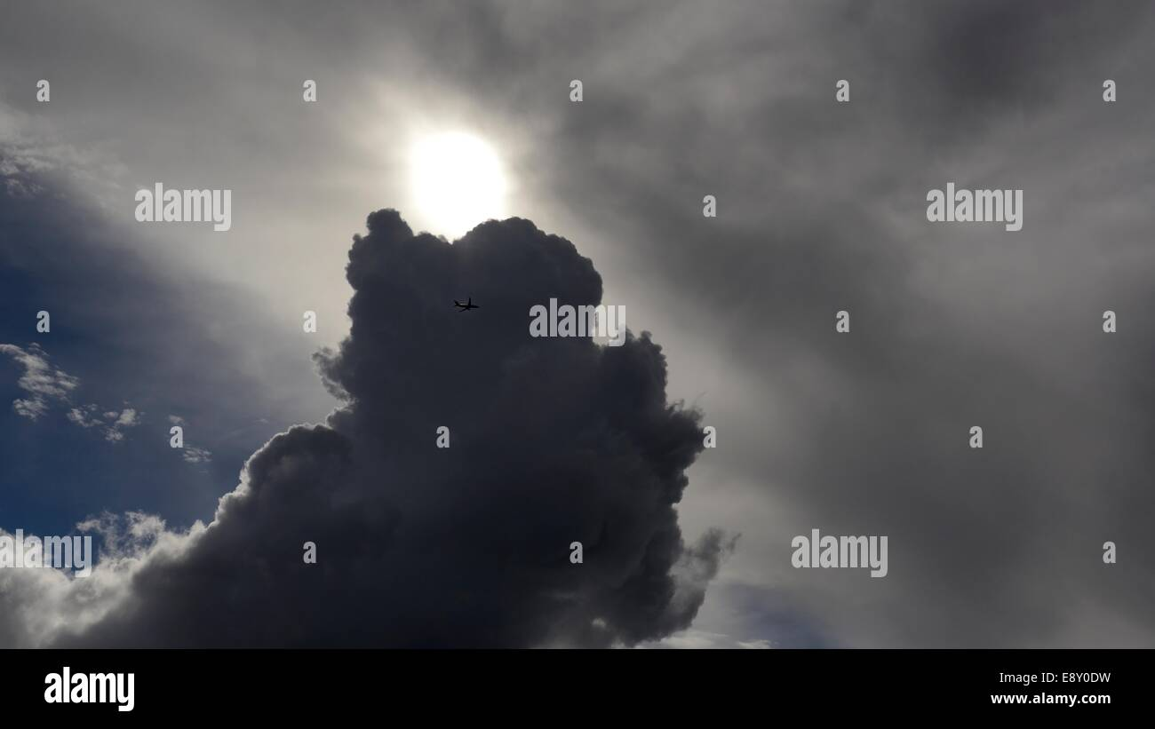 A jet airliner flying across dark storm clouds with the sun behind - Stock Image