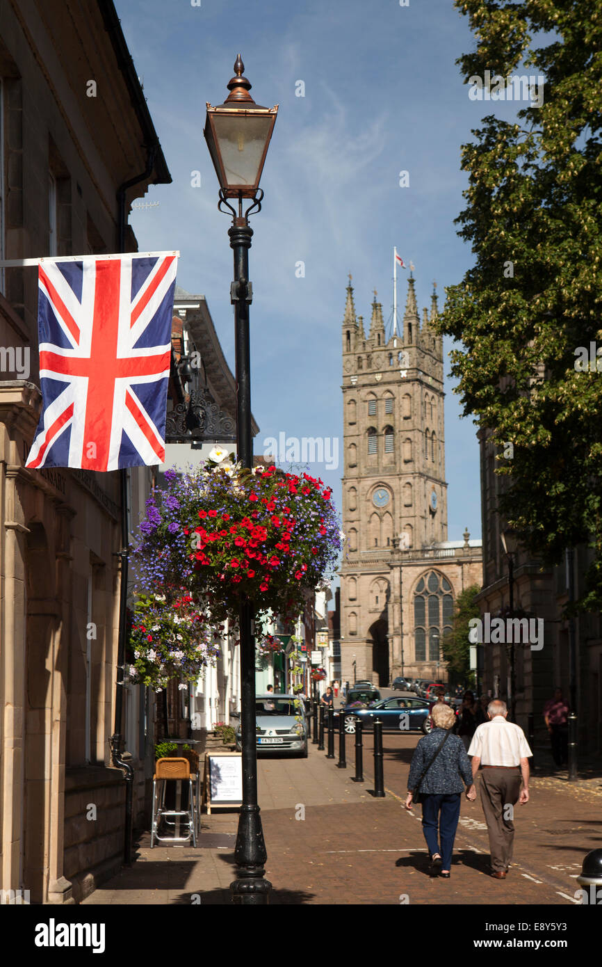 UK, England, Warwick, Church Street, union flag hanging baside floral hanging basket on old lamp post - Stock Image