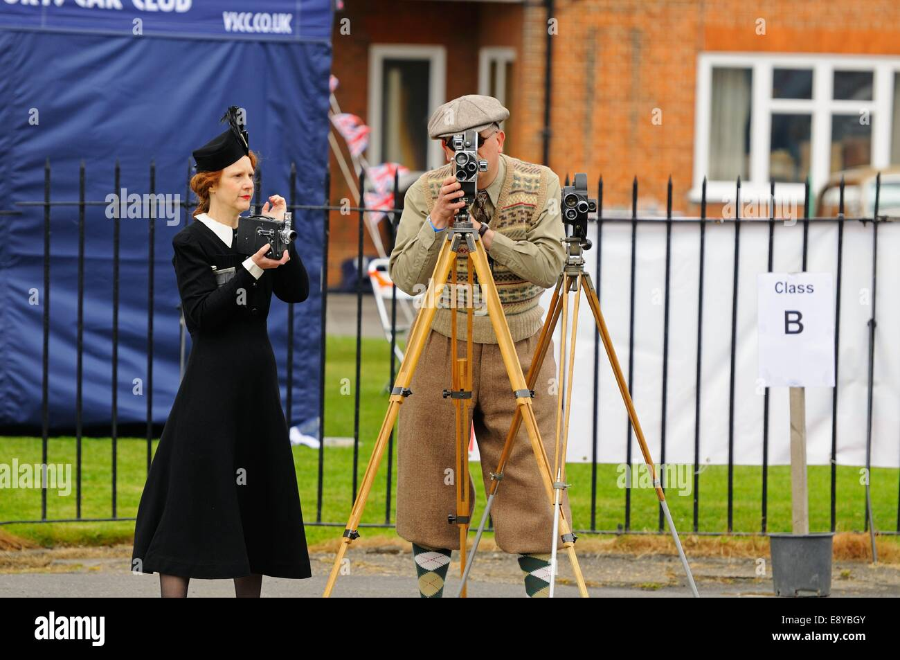 A man and wife couple in Twenties period clothing operating and loading period film cameras at an event at Brooklands - Stock Image