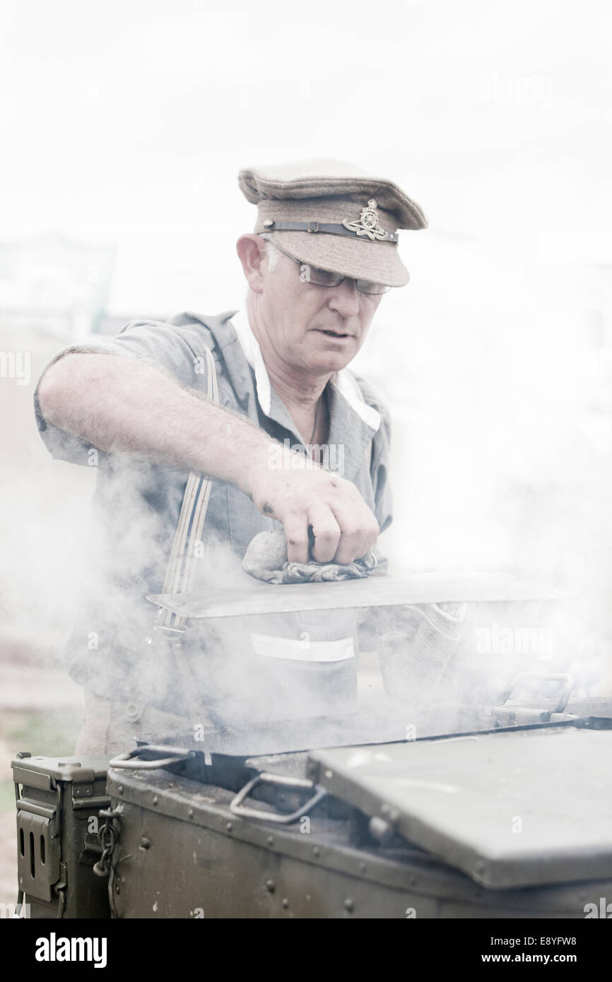 A man in WW1 British Army soldiers uniform preparing food with a horse drawn field kitchen, hot steam is rising - Stock Image