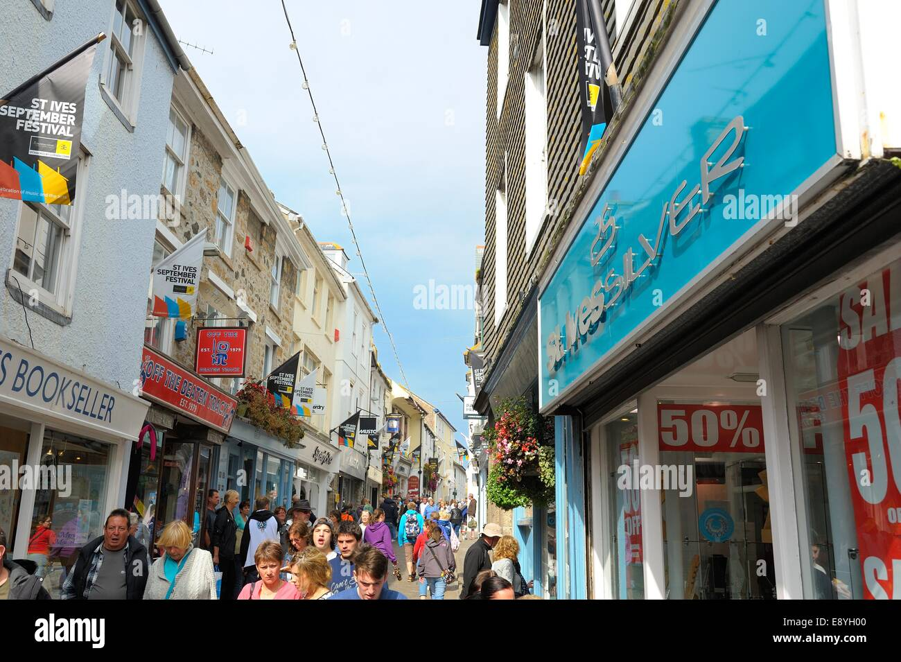 Holiday makers walking down a busy street in St Ives Cornwall England uk - Stock Image