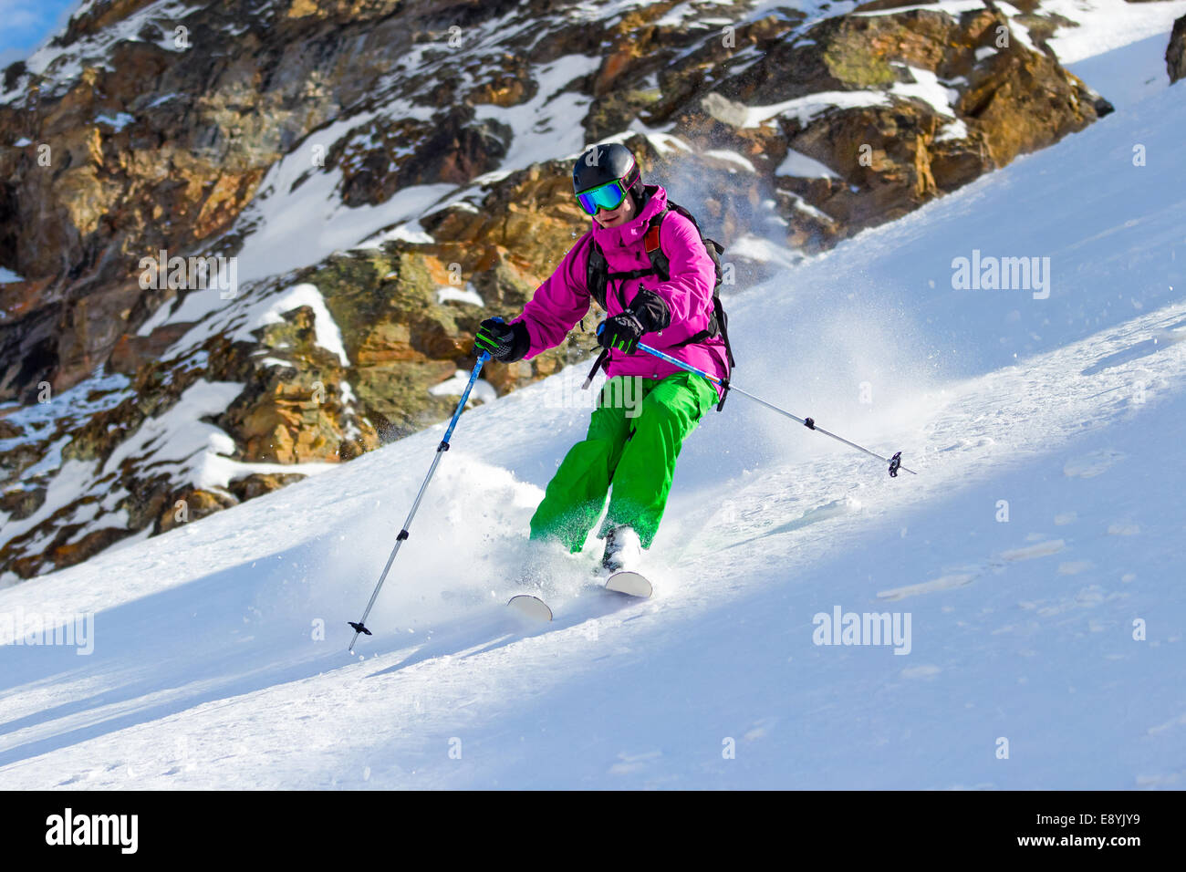 Skier at the turn on mountain steep slope off piste in soft snow on a sunny day on a background of rocks Stock Photo
