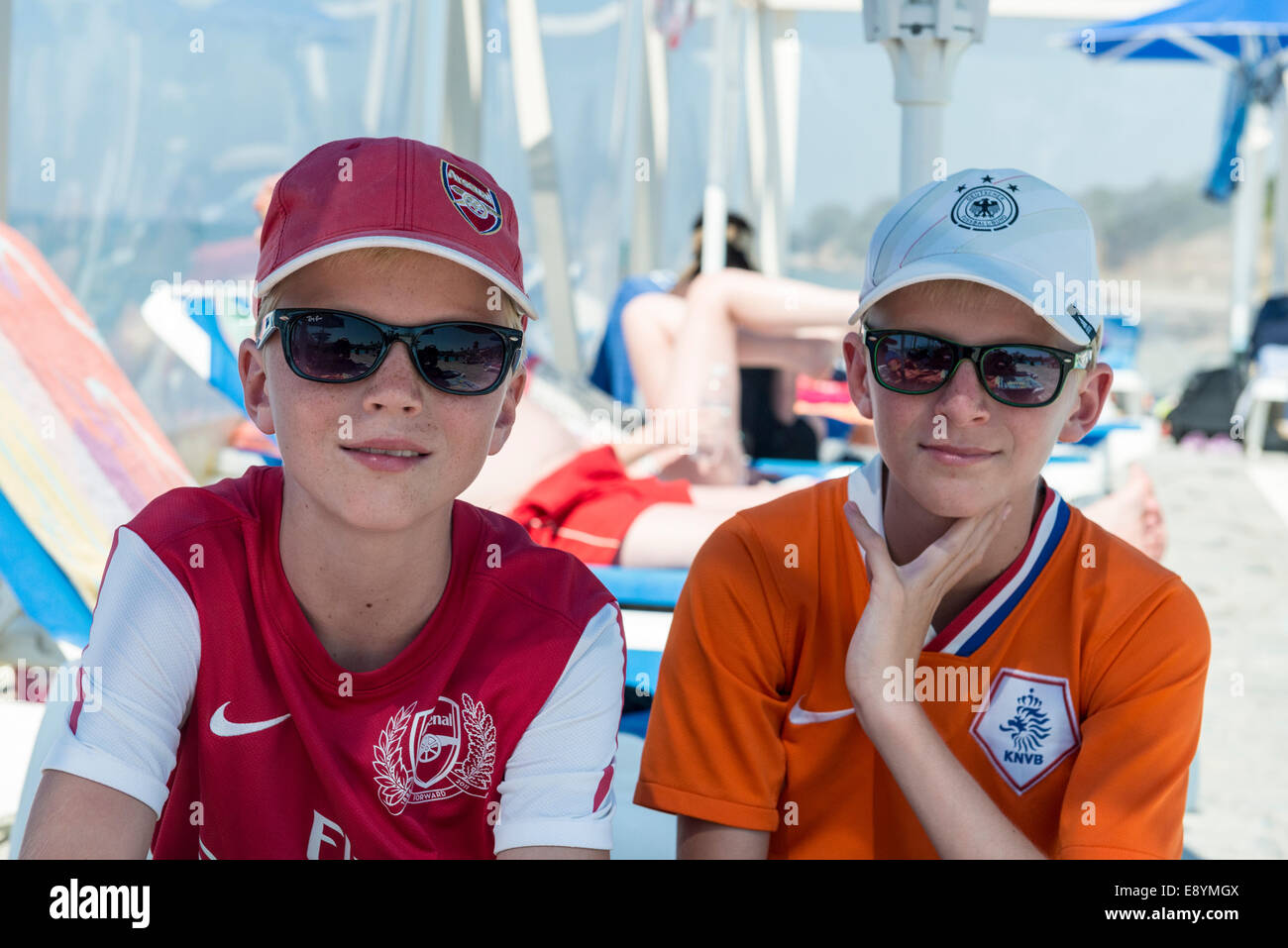 Two teenage boys with base-caps and sunglasses looking at camera Mastichari, Kos, Greece - Stock Image